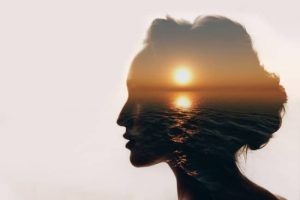 Psychology concept. Sunrise and woman silhouette.