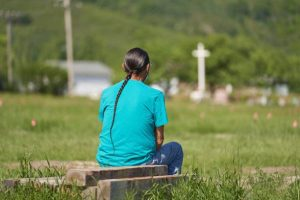 A man man sits and prays at the field where the remains of over 750 children were buried on the site of the former Marieval Indian Residential School in Cowessess First Nation, Saskatchewan, June 25, 2021. - More than 750 unmarked graves have been found near a former Catholic boarding school for indigenous children in western Canada, a tribal leader said Thursday -- the second such shock discovery in less than a month. The revelation once again cast a spotlight on a dark chapter in Canada's history, and revived calls on the Pope and the Church to apologize for the abuse suffered at the schools, where students were forcibly assimilated into the country's dominant culture. (Photo by Geoff Robins / AFP) (Photo by GEOFF ROBINS/AFP via Getty Images)