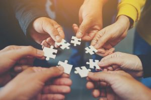 a group of people holding puzzle pieces together