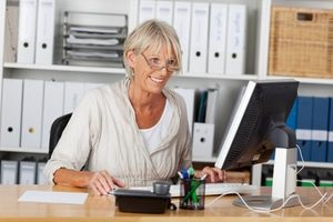 Mature worker sitting at a desk looking at a computer