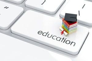 books and graduation cap sitting on a keyboard key